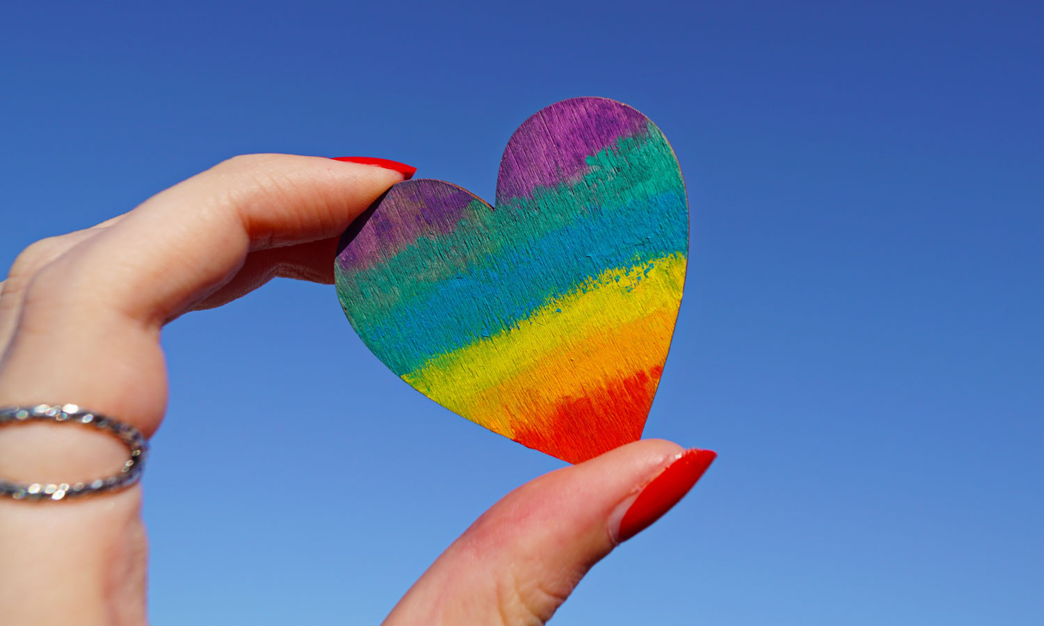 hand holding painted rainbow heart