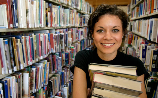 female in library holding books