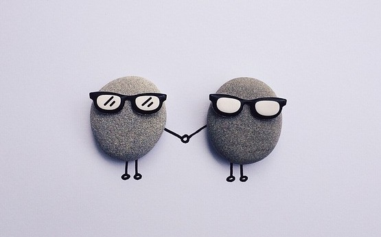 Two cartoon pebbles wearing glasses and holding hands