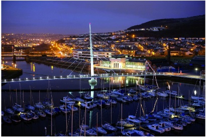 Swansea marina at night, overlooking the sail bridge with the cityscape in the background