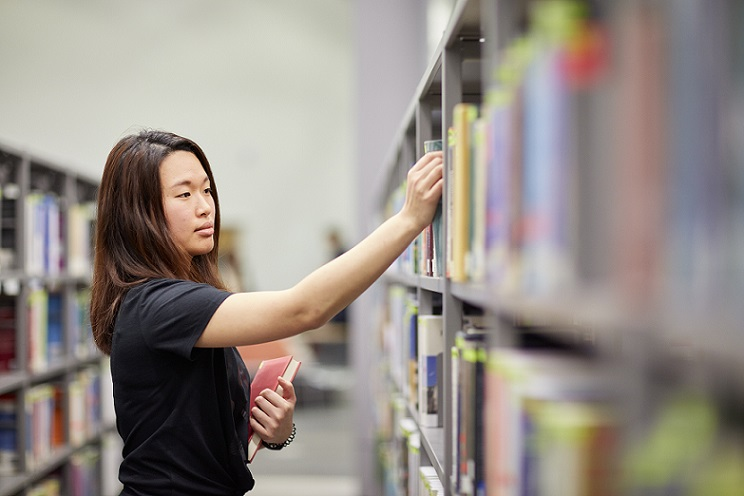 Student looking through books in the library