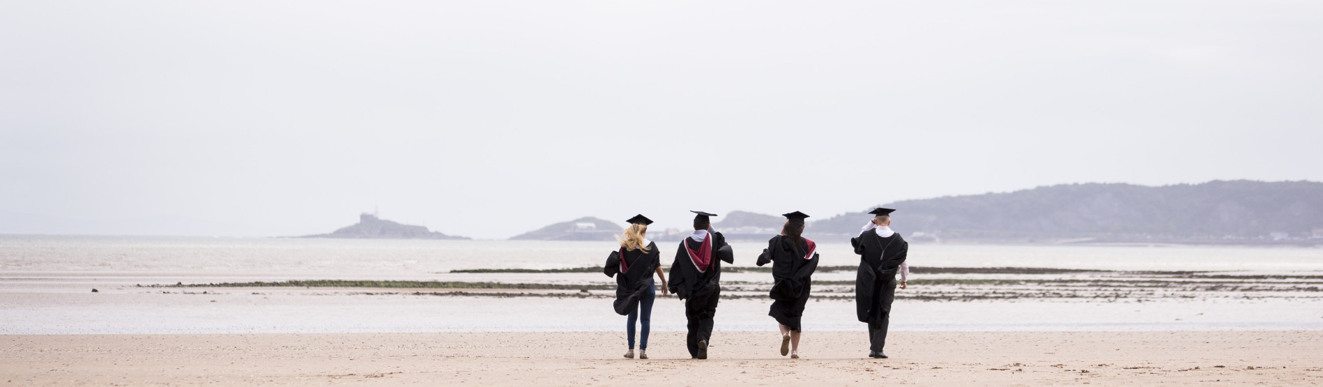 Recent graduates in robes walking away on the beach