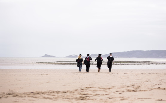 4 students in graduation robes seen walking in the distance on Swansea beach