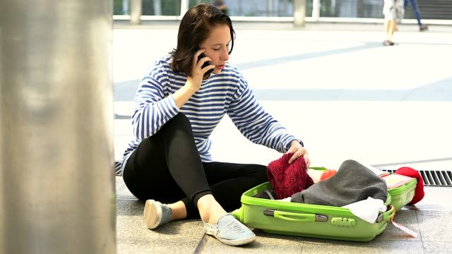 Woman searching an open suitcase and not finding what she is looking for
