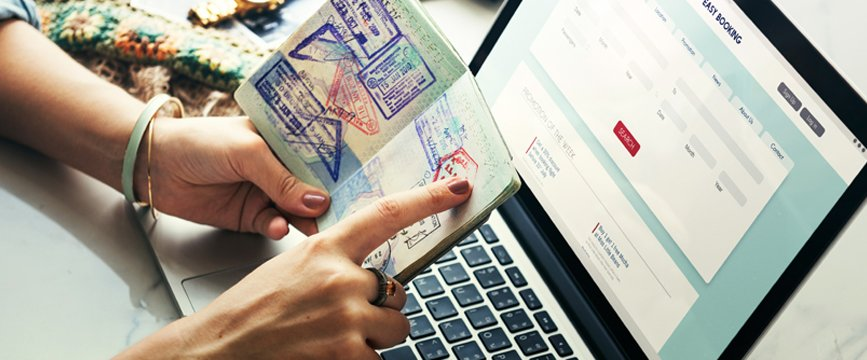 Person pointing at a passport with a computer in the background
