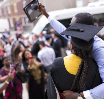 Parent and daughter taking selfie during graduation