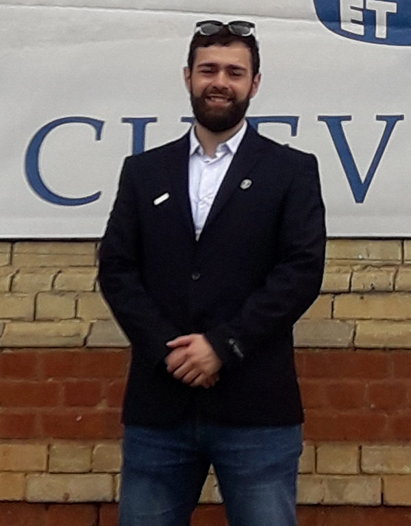 A student named Bilel standing in front of a Chevening banner