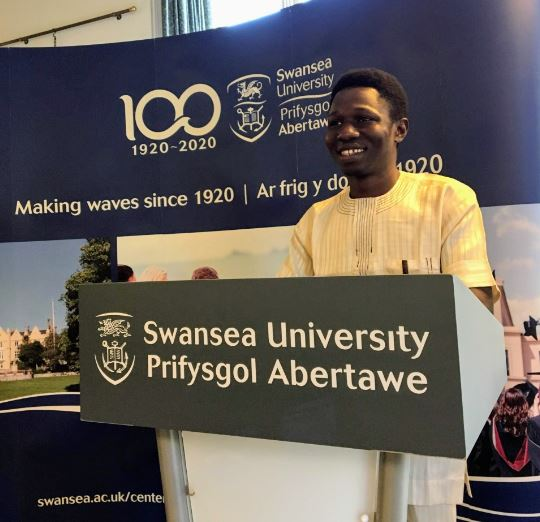 Photo of Nnadi Emmanuel Ebuka standing on a Swansea University podium