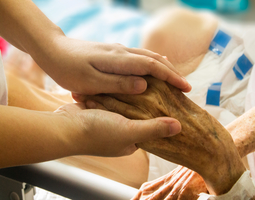 Young hand holding the hand of an elderly patient