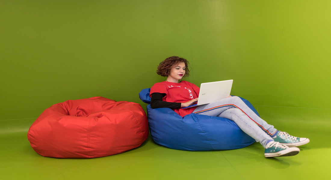 Female student working on laptop on bean bag.