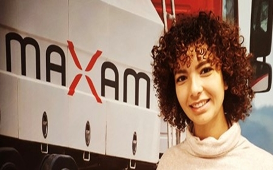 Photo of Reem standing by her new employer's, Maxam, logo.