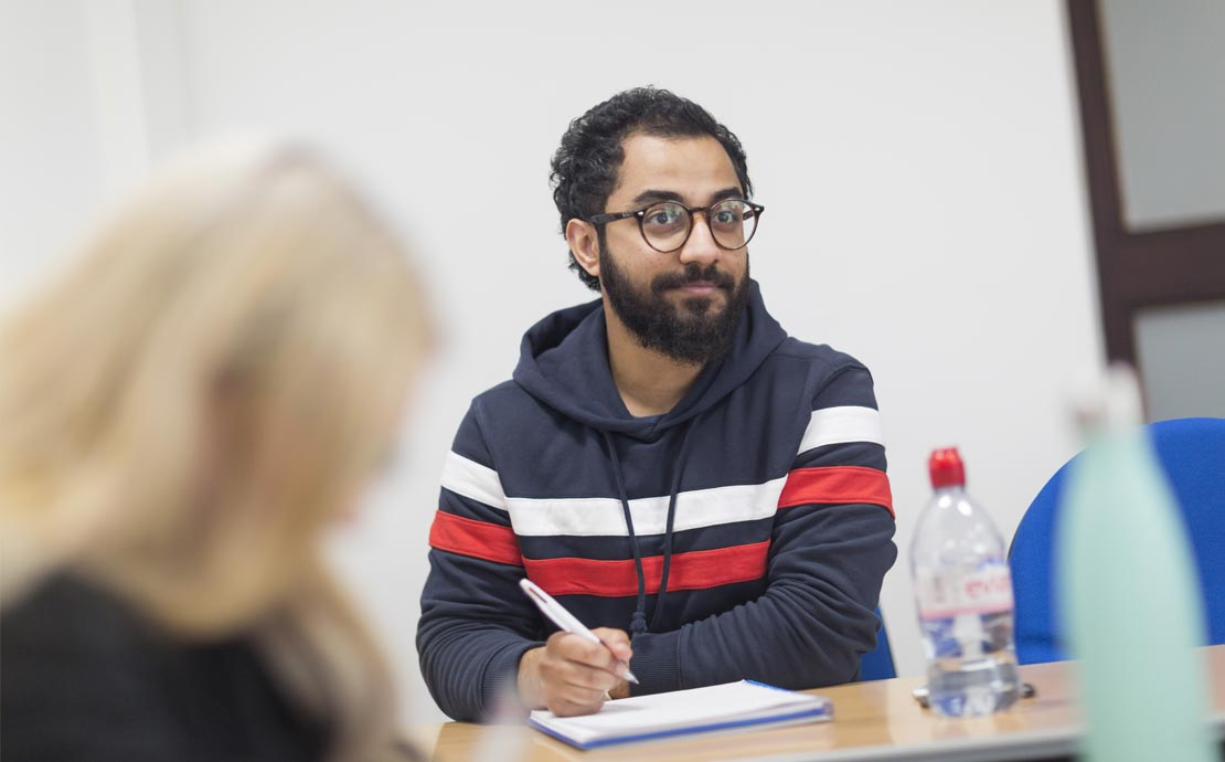 a student sitting in a lecture writing notes
