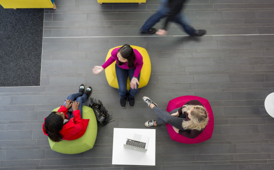 Overhead shot of three students chatting on beanbags