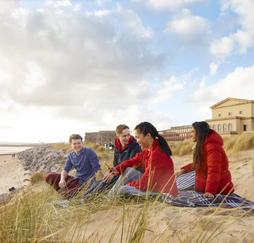 Students sitting in the dunes at Bay Campus