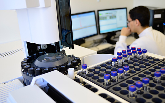 Samples in a machine with researcher on computer in the background