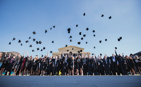 Graduates throwing their hats in front of the Great Hall.