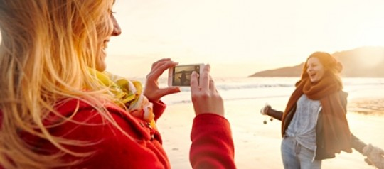 Image of graduates taking a photograph on the beach
