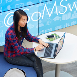 Female students sat on a laptop at a desk