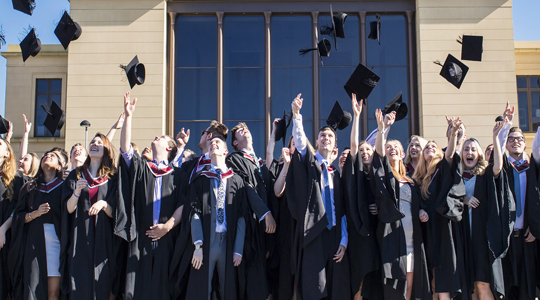 Students on graduation throwing their caps in the air