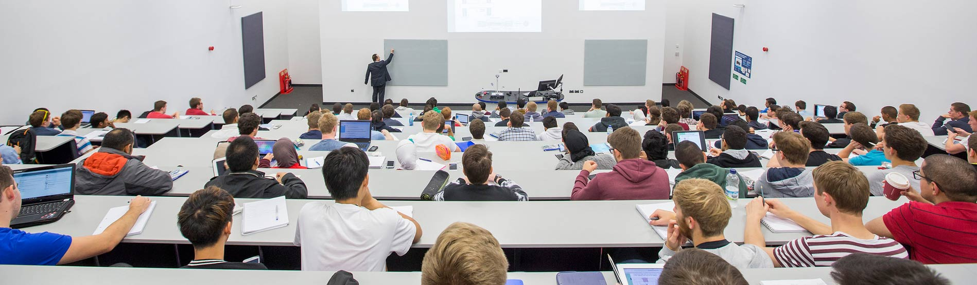A view from the back of a lecture theatre of students sat in rows and a lecturer pointing at the board at the front of the class