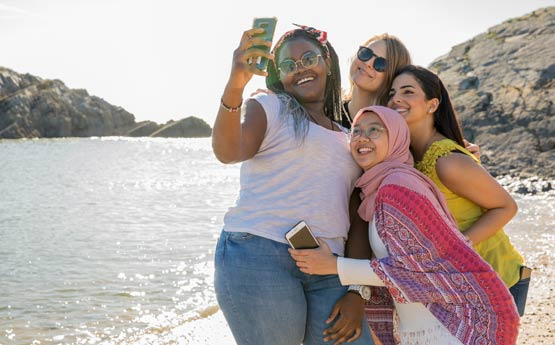 Four females on a beach taking a group selfie