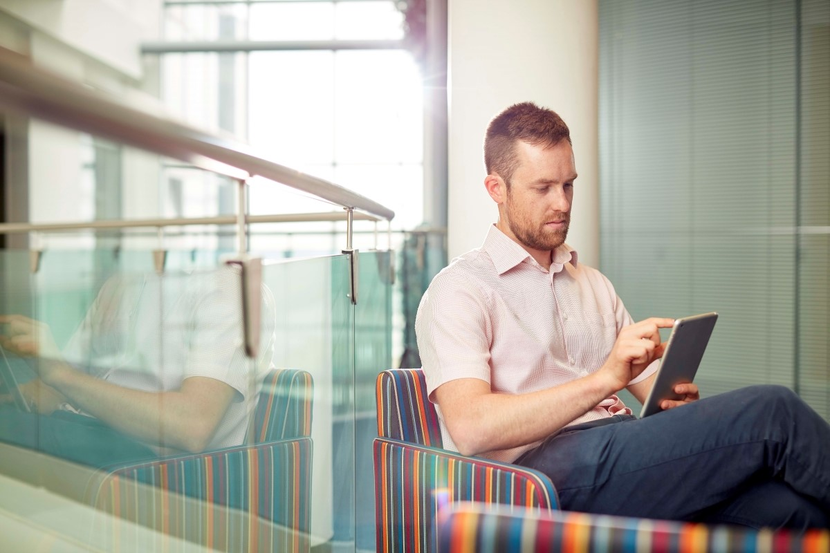 Man sitting and looking at an iPad