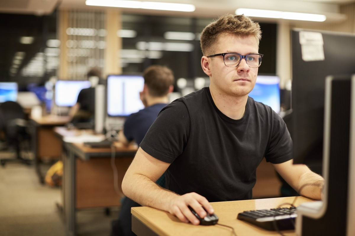 Male student wearing a black t-shirt and glasses looking sitting at a computer