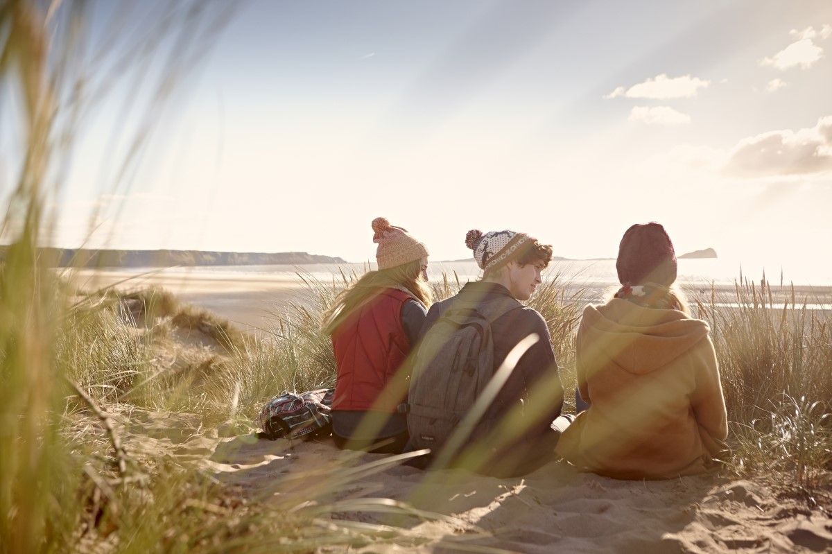 Three students sitting on a sand dune and looking across to the sea