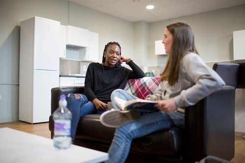 Two female students sitting on a sofa in halls of residence