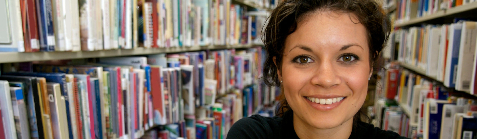 Female student in the library smiling