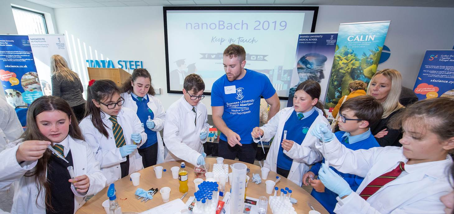 Swansea University Medical School student helping to explain nanotechnology to pupils from across Neath Port Talbot at the NanoBach event.