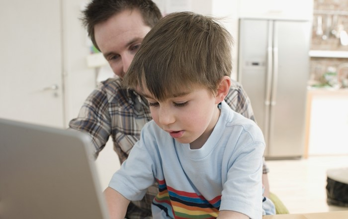 A boy at a computer with his father