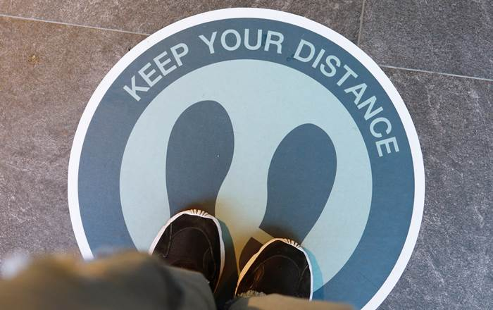 A man's feet standing on a floor sign that says 'Keep your distance'