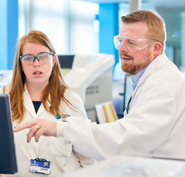 Man and woman in lab coats and goggles discussing something on a screen