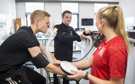 Students in sports science lab having VO2 max test on exercise bike