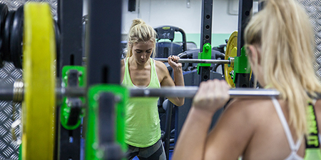 Girl concentrating on working with a large amount of weights.