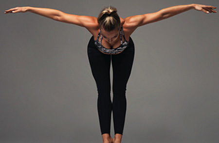 A woman is bending forward with her arms stretched out to the sides in a yoga pose like a bird