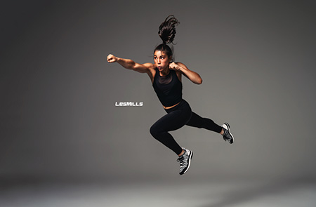 A woman dressed in exercise clothing jumps up and punches the air