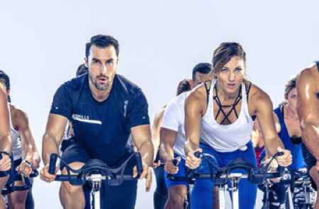 A gym class filled with people on exercise bikes, a man and woman are in the foreground and working hard