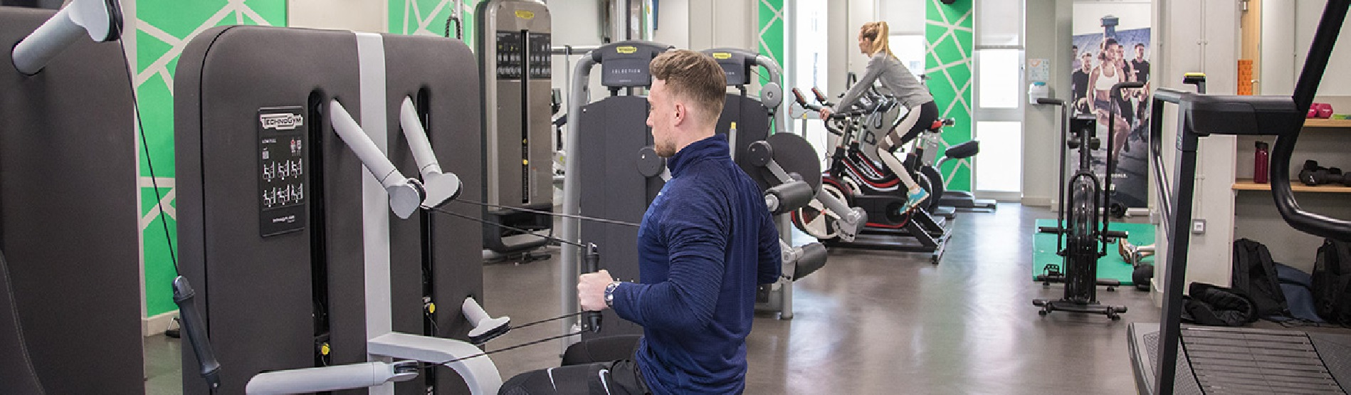 A man is exercising on a weights machine in the gym and a woman is on a bike in the background