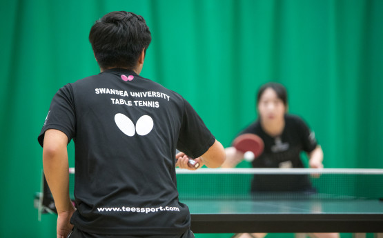 A photo two table tennis players during a rally