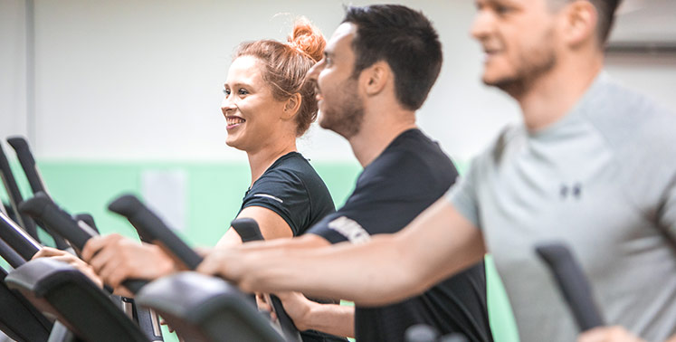 A female and 2 male students on cross trainers in the gym