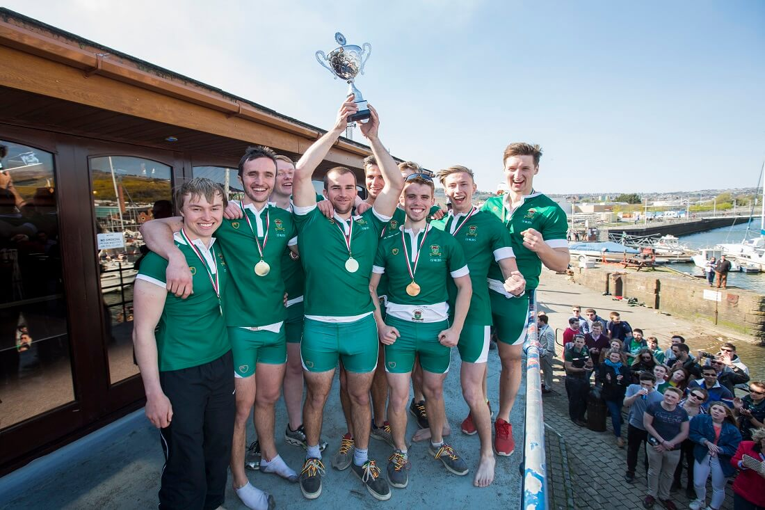 Rowing team holding up trophy