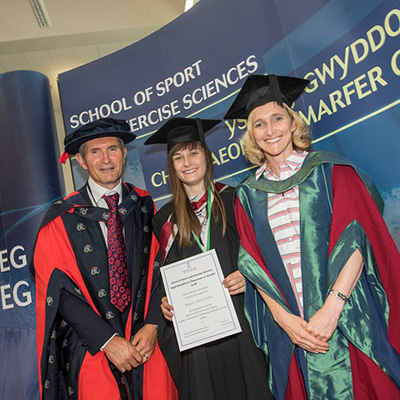 A graduate and two professors at the Graduation Reception Awards