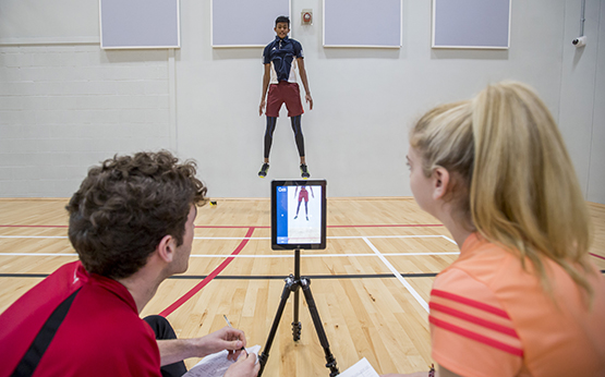 students in sports hall measuring jumps