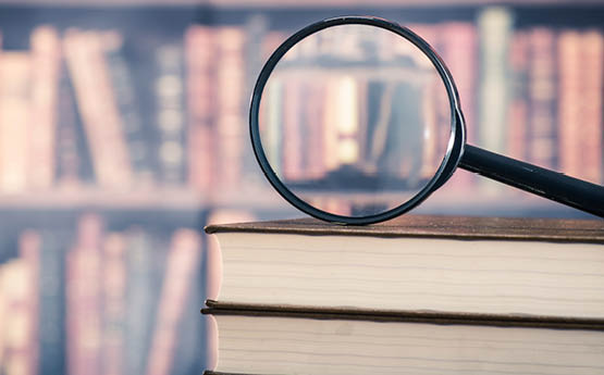 magnifying glass on top of a stack of books