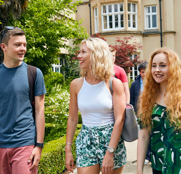 Three students walking passed the Abbey building at Swansea University