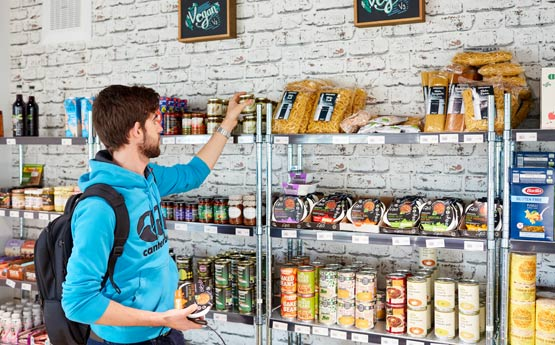 Student browsing brightly coloured food packaging in Root, Singleton Park Campus