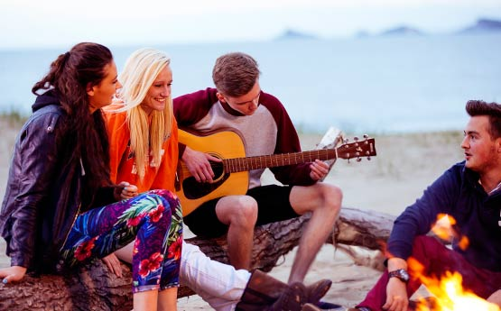 Friends gathered around a campfire by the beach with a boy playing guitar