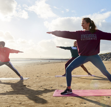 students doing yoga on the beach